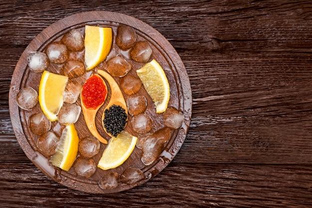 Vista superior do caviar de esturjão preto e salmão vermelho na mesa de madeira