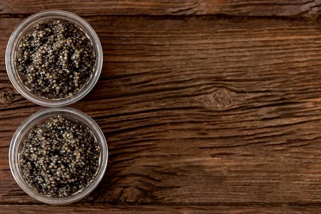 Vista superior do caviar de esturjão preto ou beluga na mesa de madeira