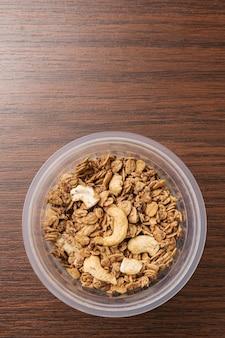Vista superior do cereal de granola crocante orgânico com aveia e caju dentro de um copo de plástico.