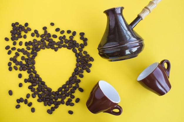 Vista superior do cezve turco, xícaras marrons e grãos de café em forma de calor
