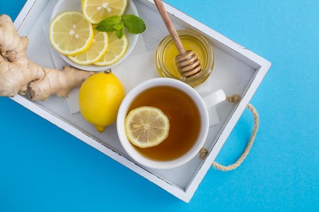 Vista superior do chá com limão, mel e gengibre na bandeja branca