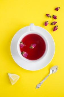 Vista superior do chá com rosas cor de rosa na xícara branca Foto Premium
