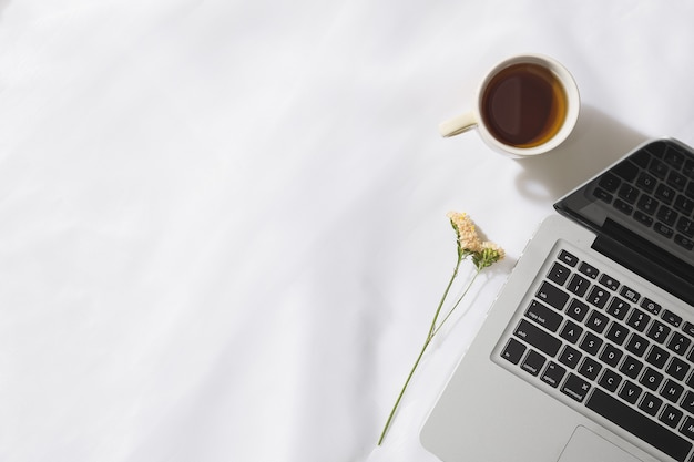 Vista superior do chá da manhã no fundo do tecido de voile com um laptop, caneca de chá e uma flor com espaço para texto