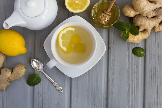 Vista superior do chá de gengibre e ingredientes na superfície cinza