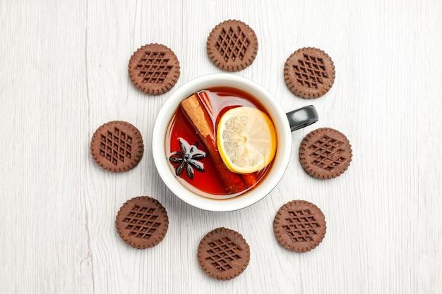 Vista superior do chá de limão e canela arredondado com biscoitos na mesa de madeira branca