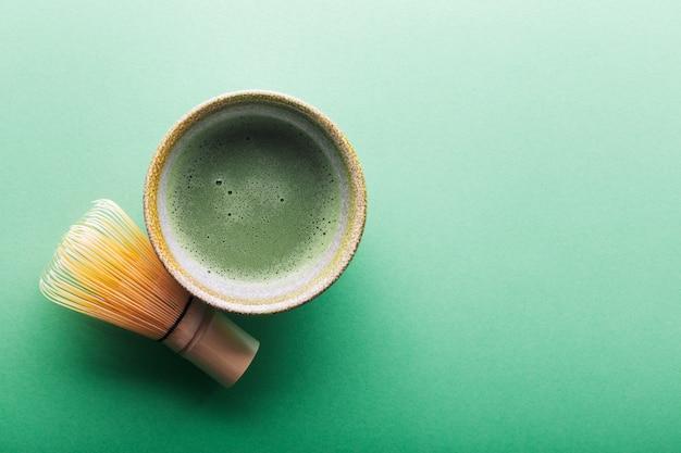 Vista superior do chá matcha em uma tigela e chasen na superfície greeen