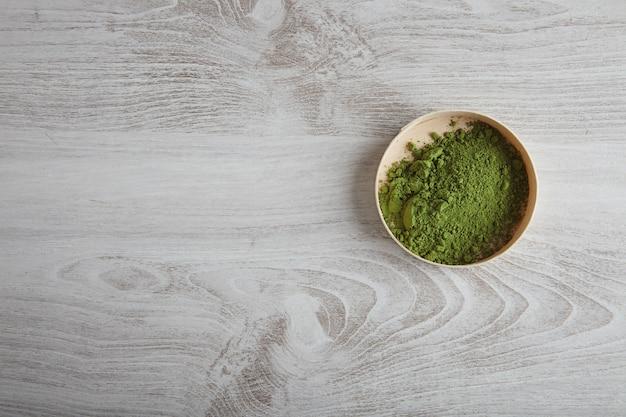 Vista superior do chá matcha orgânico premium em pó em uma caixa de madeira isolada na mesa branca simples