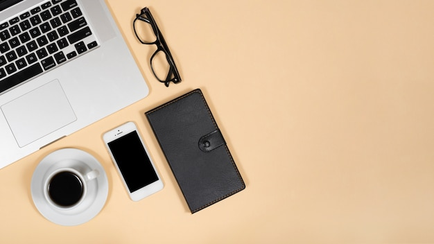 Vista superior do chá quente; celular; óculos; diário e laptop sobre fundo bege