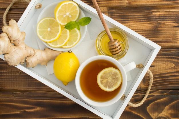 Vista superior do chá verde com limão, mel e gengibre na bandeja branca na mesa de madeira, close-up