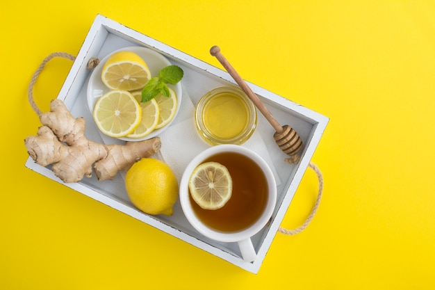 Vista superior do chá verde com limão, mel e gengibre na bandeja de madeira branca na superfície amarela