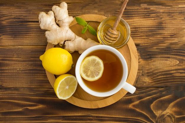 Vista superior do chá verde com limão, mel e gengibre na tábua de madeira