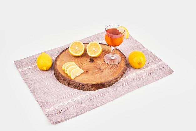 Vista superior do chá verde com limões na toalha de mesa marrom.