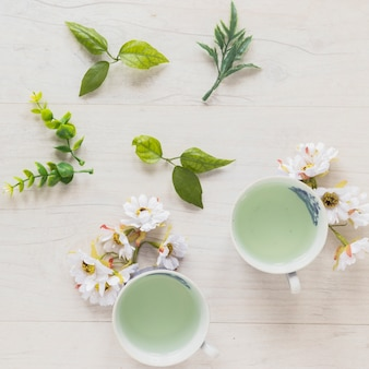 Vista superior do chá verde em xícaras com folhas e flores frescas