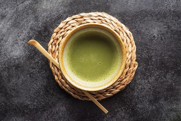 Vista superior do chá verde matcha em uma tigela na mesa escura