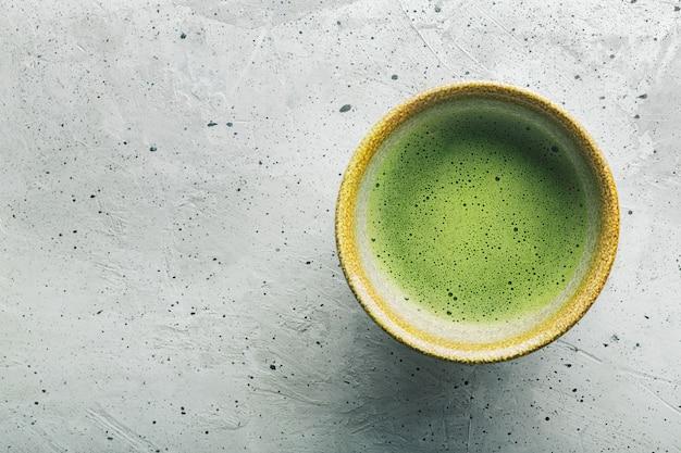 Vista superior do chá verde matcha em uma tigela na superfície de concreto