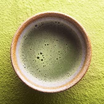 Vista superior do chá verde matcha em uma tigela sobre uma superfície em pó