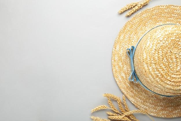 Vista superior do chapéu de palha de praia com fita azul e espigas na superfície cinza