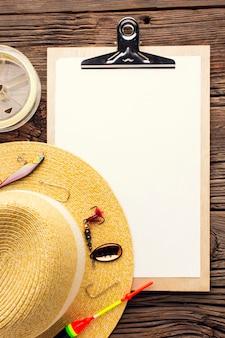 Vista superior do chapéu de pesca com isca e bloco de notas