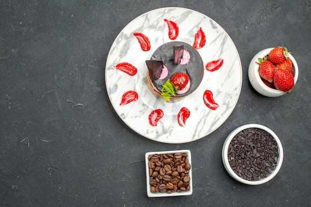Vista superior do cheesecake de morango em tigelas de prato oval com sementes de morango e chocolate e café na superfície escura