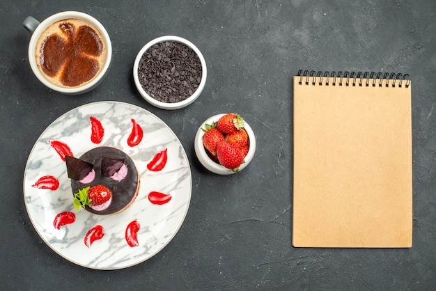 Vista superior do cheesecake de morango em uma tigela oval branca com morangos e chocolate uma xícara de café um caderno na superfície escura