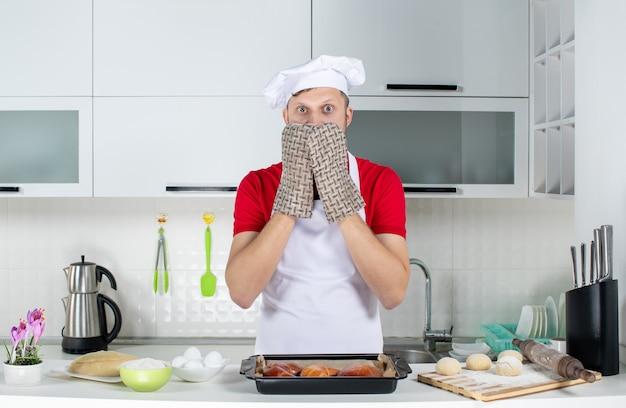 Vista superior do chef assustado usando o suporte em pé atrás da mesa com um ralador de ovos de confeitaria na cozinha branca