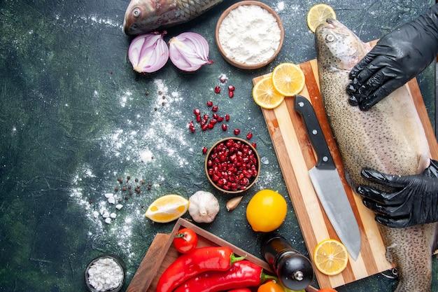 Vista superior do chef com luvas pretas segurando peixe cru na tábua de madeira moedor de pimenta farinha tigela sementes de romã na tigela na mesa da cozinha