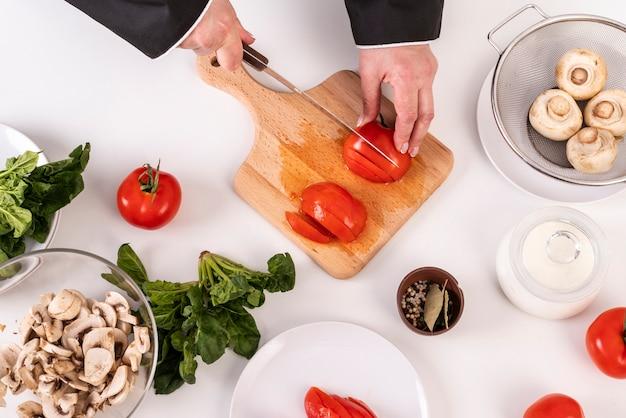 Vista superior do chef feminino cortar tomates