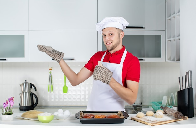 Vista superior do chef masculino confiante usando o suporte em pé atrás da mesa com um ralador de ovos de confeitaria e mostrando algo do lado direito na cozinha branca