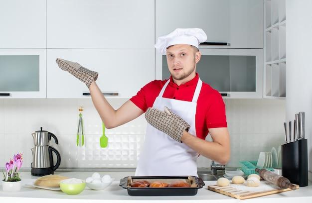 Vista superior do chef masculino usando o suporte em pé atrás da mesa com um ralador de ovos de confeitaria e mostrando algo do lado direito na cozinha branca