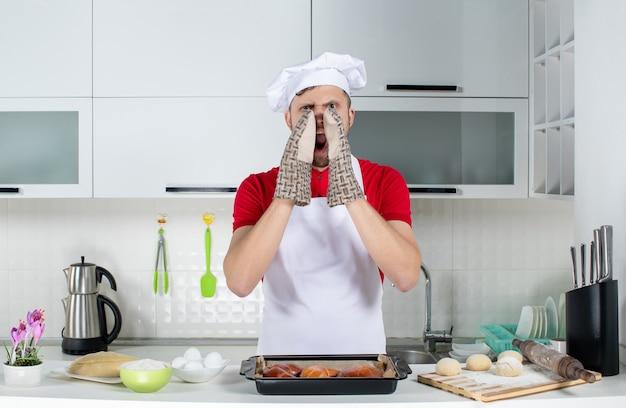 Vista superior do chef masculino usando o suporte em pé atrás da mesa com um ralador de ovos e doces e chamando alguém na cozinha branca