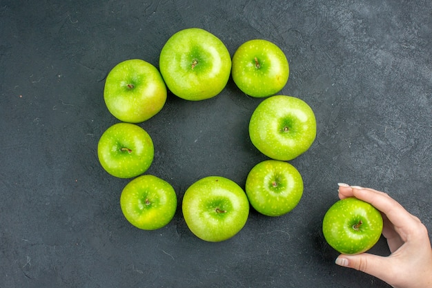 Vista superior do círculo linha maçã verde maçã na mão da mulher na mesa escura