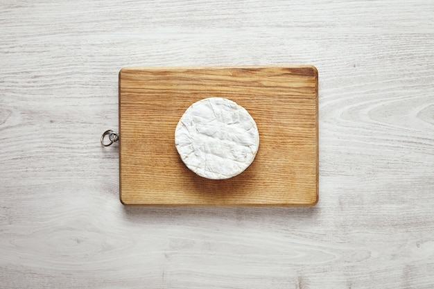 Vista superior do círculo perfeito de queijo camembert na placa de madeira rústica isolada na mesa de madeira branca envelhecida no centro