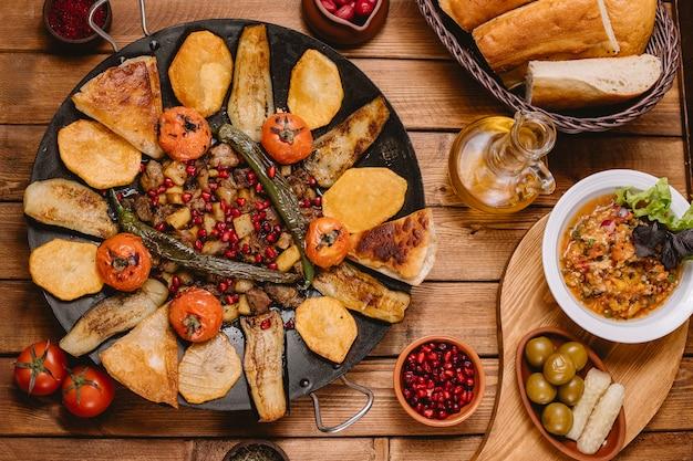 Vista superior do cizbiz saj azerbaijano cozido com tomate e pimenta de batata berinjela na panela de ferro fundido