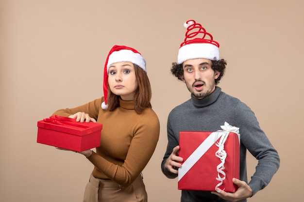 Vista superior do clima de ano novo e conceito de festa - casal adorável confuso segurando presentes usando chapéus de papai noel