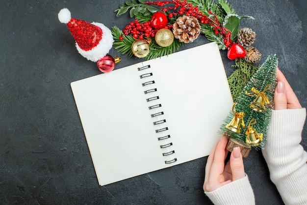 Vista superior do clima de natal com a mão do chapéu de papai noel com galhos de pinheiro segurando uma árvore de natal em fundo escuro