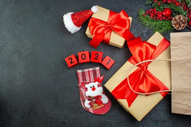 Vista superior do clima de natal com lindos presentes com fita vermelha e números de meia de natal com chapéu de papai noel em fundo escuro