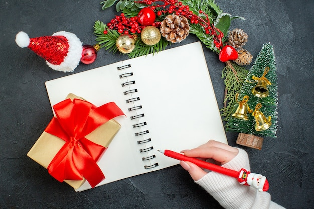 Vista superior do clima de natal com ramos de pinheiro chapéu de papai noel, mão segurando a caneta no caderno em fundo escuro