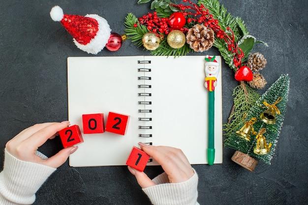 Vista superior do clima de natal com ramos de pinheiro chapéu de papai noel números da árvore de natal no caderno em fundo escuro