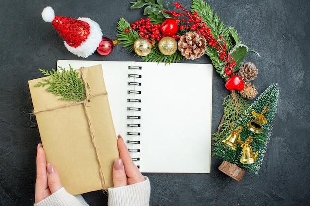 Vista superior do clima de natal com ramos de pinheiro e chapéu de papai noel segurando uma caixa de presente em fundo escuro