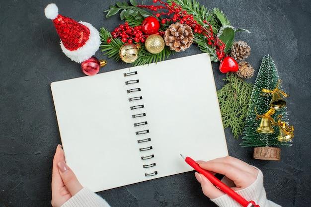 Vista superior do clima de natal com ramos de pinheiro xsmas árvore chapéu de papai noel, mão segurando uma caneta no caderno espiral em fundo escuro