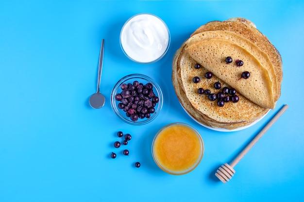 Vista superior do close-up da culinária nacional russa e panquecas de sobremesa com creme de leite, frutas e mel. prato tradicional para entrudo. foco seletivo. copie o espaço.