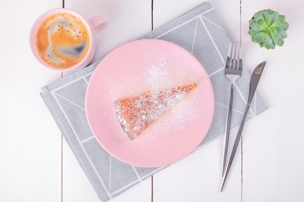 Vista superior do close-up de um pedaço de torta em um prato rosa com uma faca e um garfo em um guardanapo de linho dobrado com um padrão geométrico e uma caneca com café. cozimento caseiro. foco seletivo.