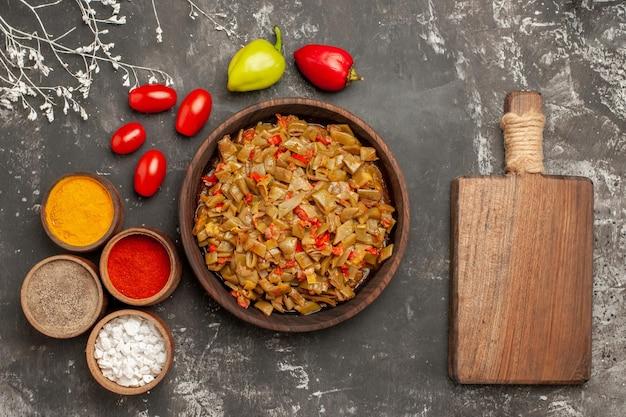 Vista superior do close-up feijão verde e especiarias feijão verde no prato especiarias coloridas, tomates e pimentões ao lado da placa de madeira da cozinha na mesa
