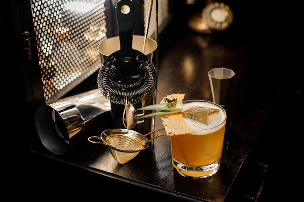 Vista superior do cocktail de verão alcoólico decorado amarelo fresco e azedo e utensílios dispostos na mesa do bar