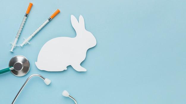 Vista superior do coelho de papel com seringas e estetoscópio para o dia animal