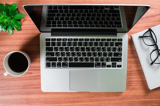 Vista superior do computador e dos vidros no livro branco.