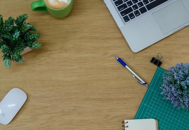Vista superior do computador laptop, mouse, flor, bloco de notas e caneta na mesa de madeira.