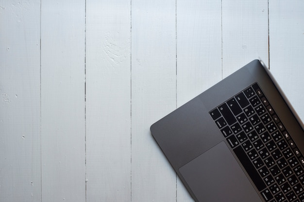 Vista superior do computador portátil em fundo branco de madeira