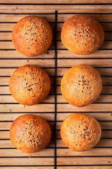 Vista superior do conceito de comida, pães de hambúrguer caseiros recém-assados em fundo de madeira com espaço de cópia