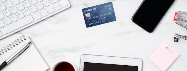 Vista superior do conceito de compras online com cartão de crédito e eletrônicos isolados no fundo da mesa branca de mármore do escritório.